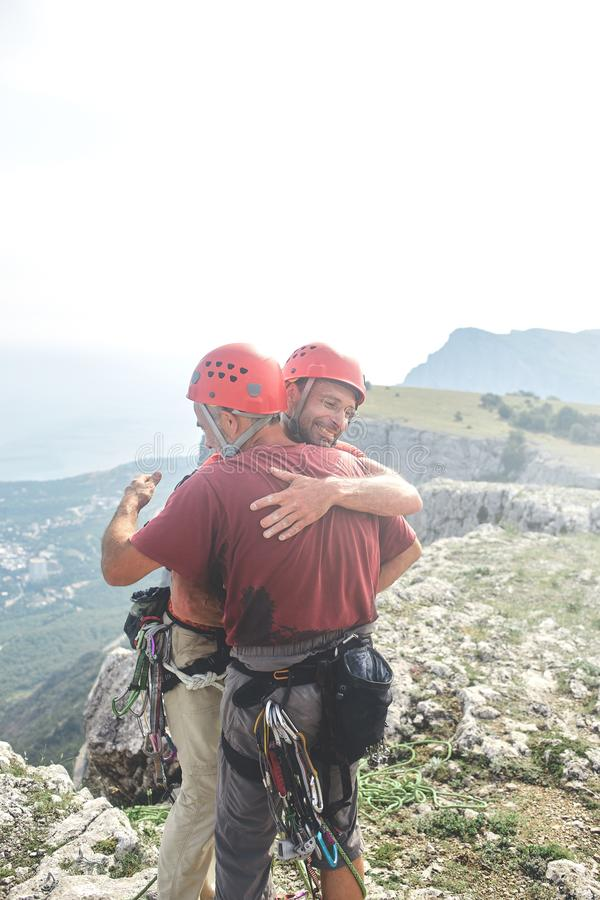 Two man rock climbers climbed on the cliff. Two men rock climbers climbed on the cliff. happy climbers on the top of the mountain. friends hug and congratulate royalty free stock images