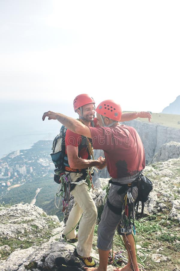 Two man rock climbers climbed on the cliff. Two men rock climbers climbed on the cliff. happy climbers on the top of the mountain. friends hug and congratulate stock photography