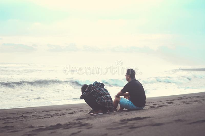 Two Man Sitting on the Sand Near the Beach stock photography