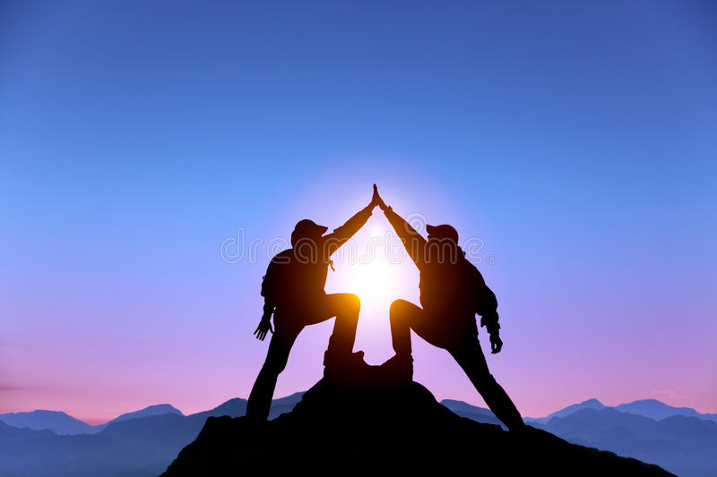 Two man with success gesture on the mountain. The Silhouette of two men with success gesture standing on the top of mountain stock image