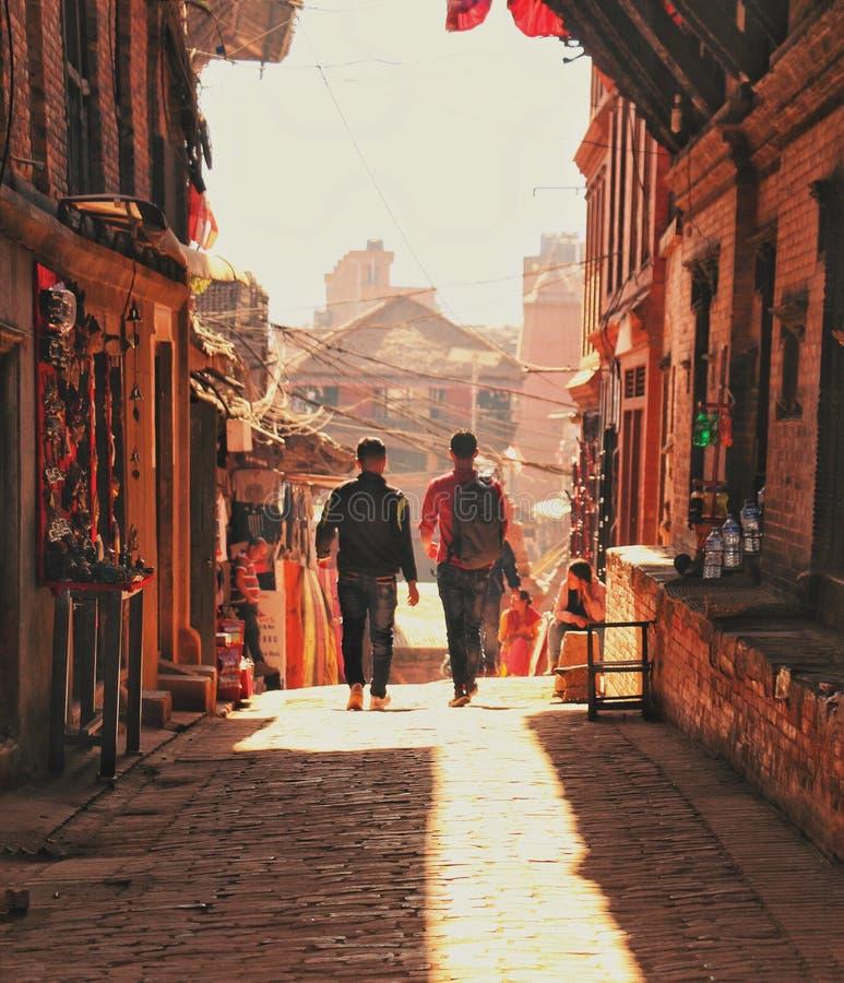 Two Man Walking Beside Brick Houses stock photo