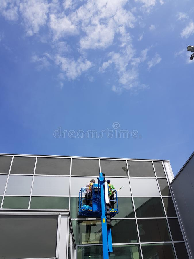 Two man washing windows from cherry picker Shopping mall stock photos