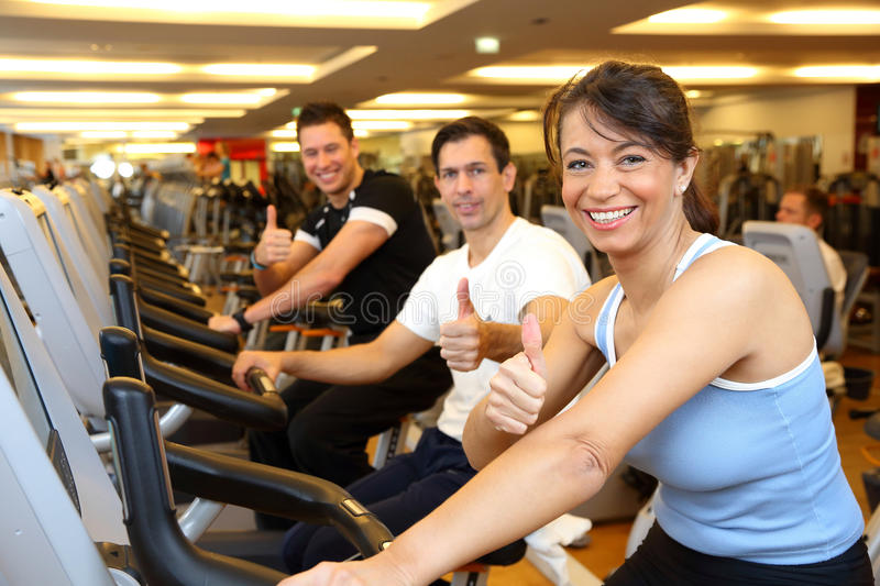 Two man and woman on exercise bikes with thumbs up royalty free stock image