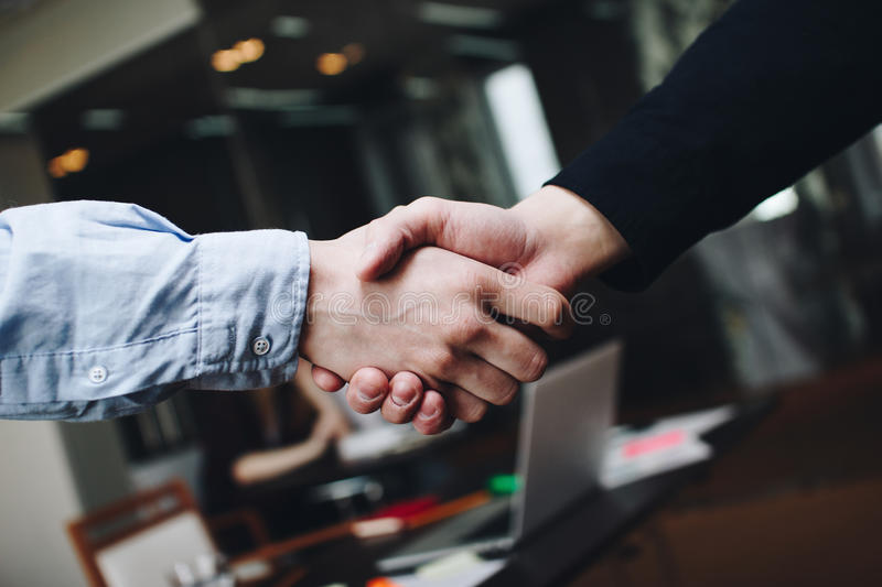 Two managers in casual clothing in meeting room handshakes after finding compromise. Blurred background royalty free stock images