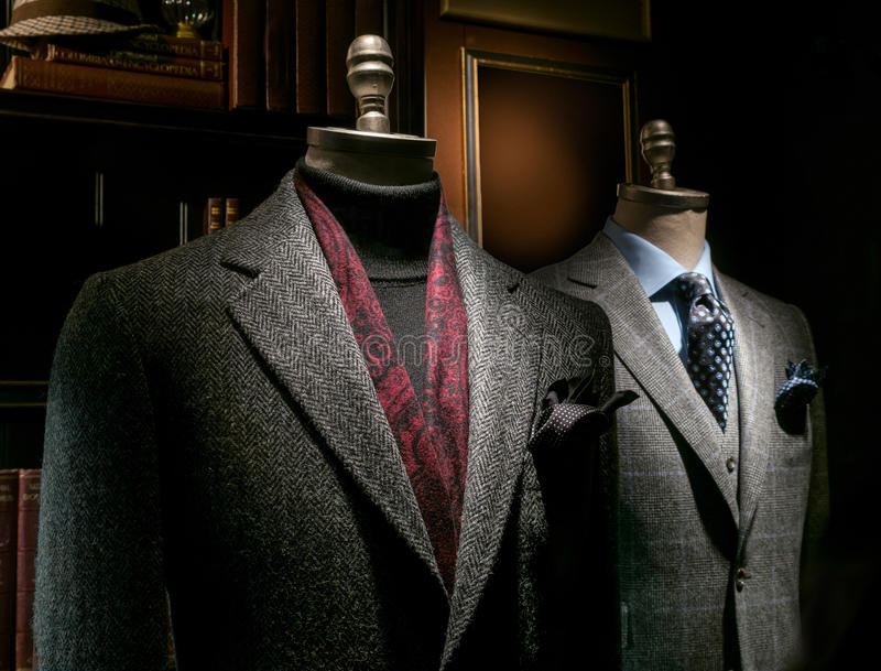 Two Mannequins in Coat and Suit. Two mannequin in a tailor's shop: one in gray coat, black sweater and red scarf, another one in gray checkered suit stock image