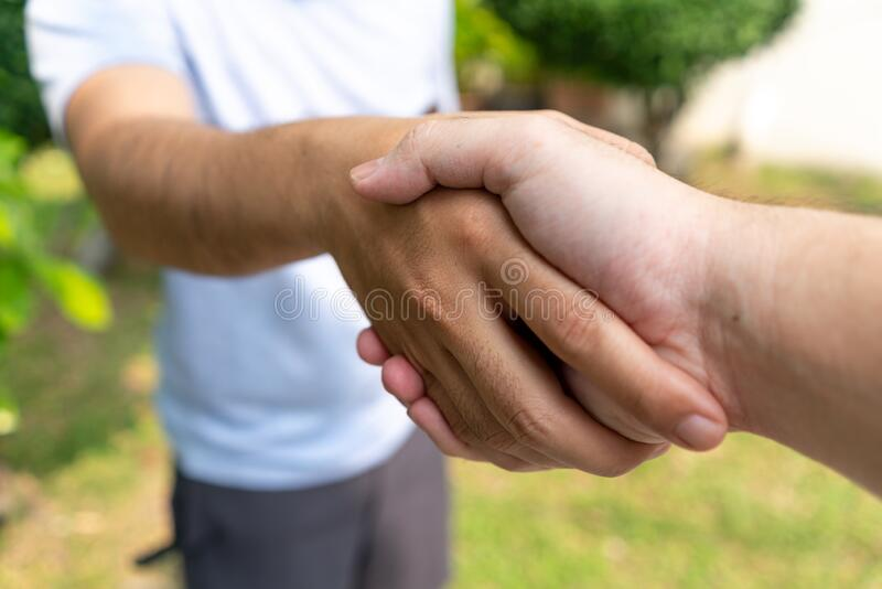 Two mans are hands shake together with deal in business or trust. Friend are Hand clasp in park. Conceptual of teamwork or deal in business with copy space royalty free stock photography