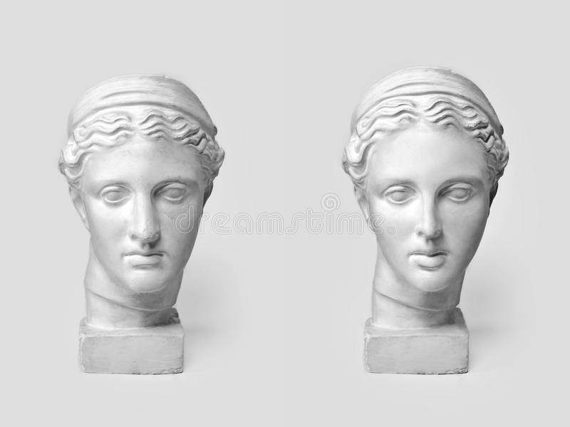 Two marble heads of young women, ancient Greek goddess bust before plastic surgery and after operation on light. Background. Old and new beauty standarts stock images