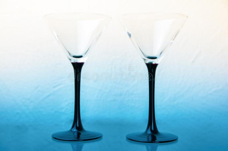 two martini glasses on black legs on a white-blue background royalty free stock images
