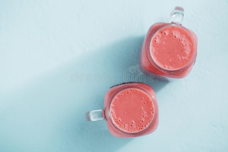 Two mason jars with strawberry smoothie on blue pastel background. Top view with copy space. Healthy berry milkshake in glasses stock photo