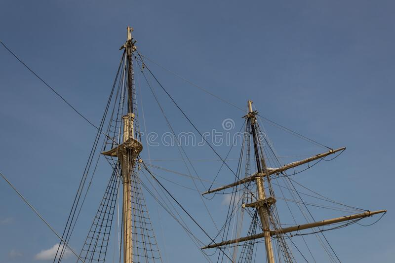 Two masts, rigging and shrouds on an old tall ship against a blue sky. Horizontal aspect royalty free stock image