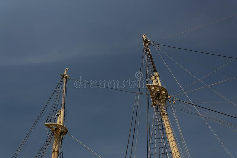 Two masts and rigging of a vintage tall ship before gloomy dark sky, marine themed backdrop. Horizontal aspect stock photography