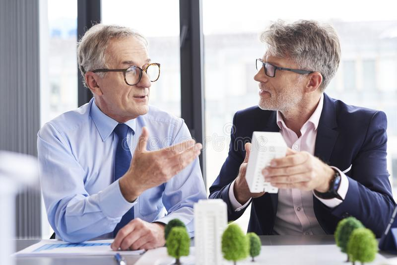 Two mature architects discussing business strategy royalty free stock photo