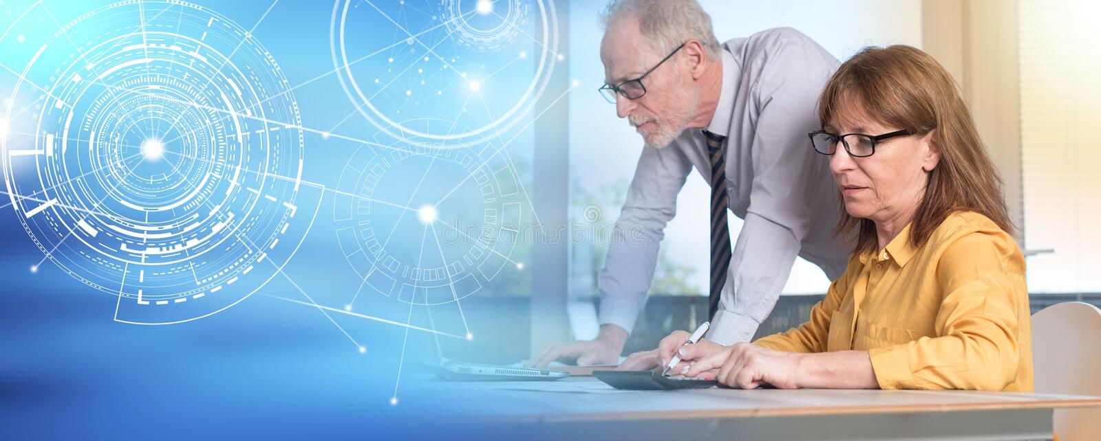 Two mature business people working together; light effect stock photo