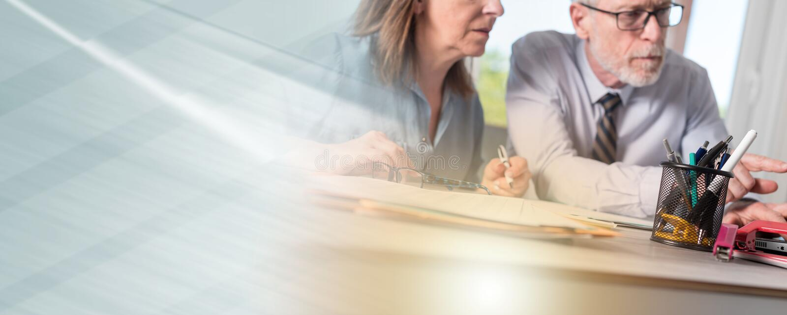 Two mature business people working together; panoramic banner royalty free stock images