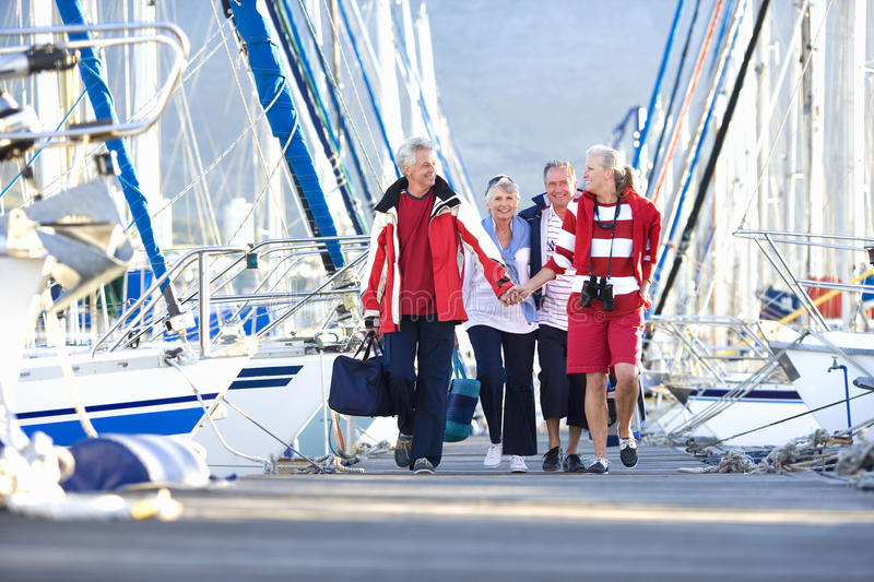Two mature couples walking affectionately along harbour jetty past moored yachts, man carrying bag, smiling, front view royalty free stock photography