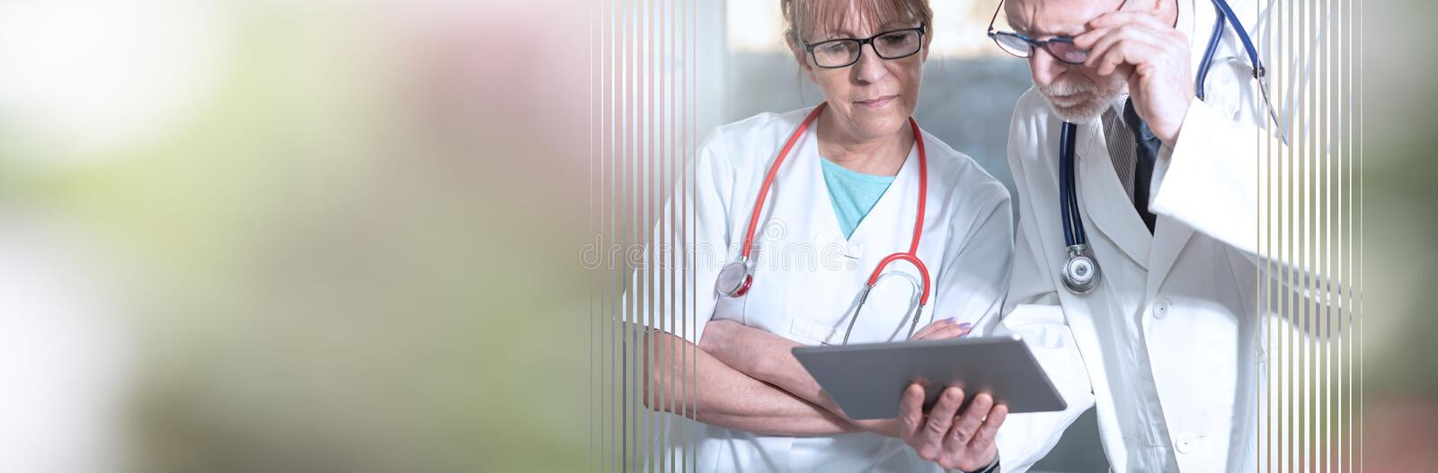 Two doctors discussing about medical report on tablet; panoramic banner stock photography