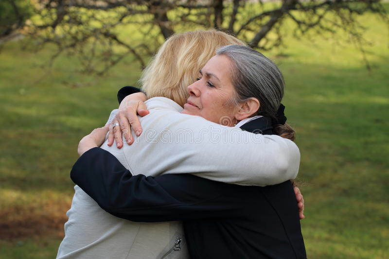 Two mature friends hugging stock photos