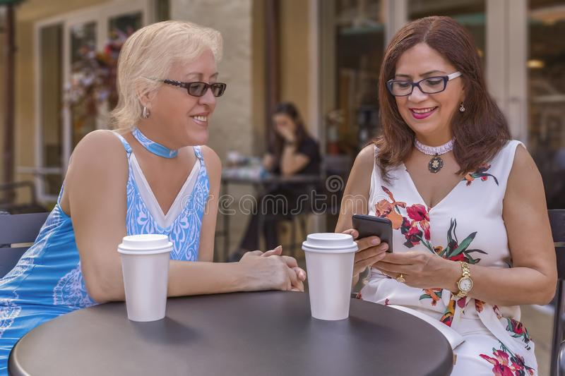 Two mature friends enjoy coffee outdoors while looking at the smartphone stock image