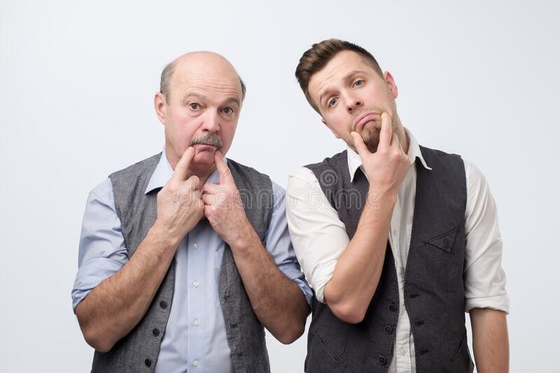 Two mature men father and son being sad. Negative facial emotion royalty free stock photo