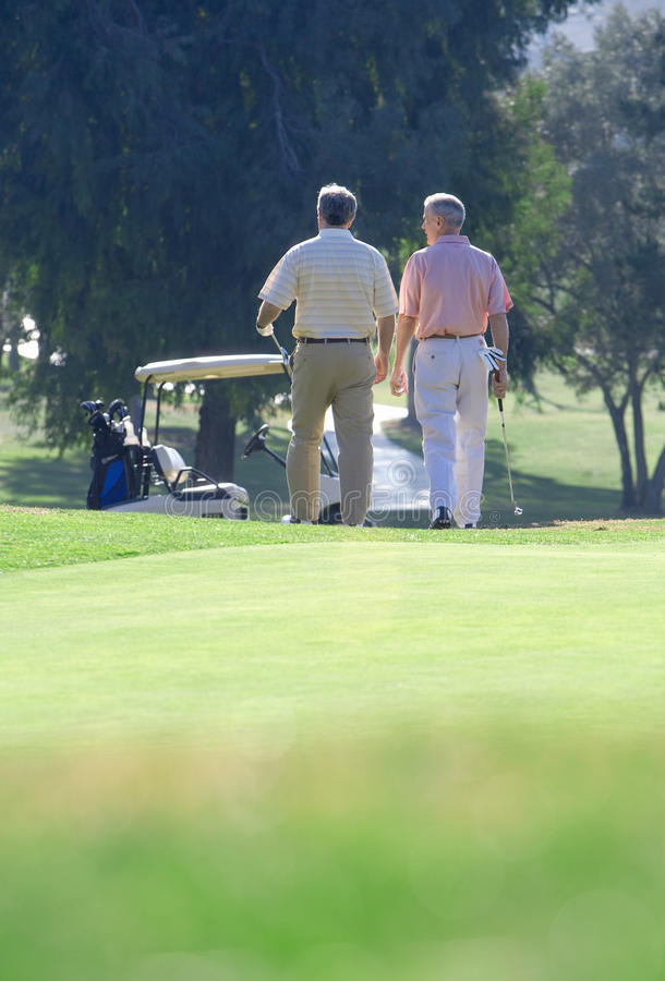Two mature men leaving putting green on golf course, approaching parked golf buggy in mid-distance, rear view, focus on background stock images