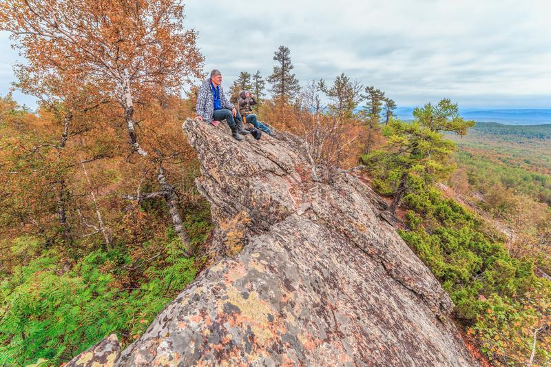 Two mature tourists are sitting on top of a rock. And looking out into the distance to the mountains stock photography