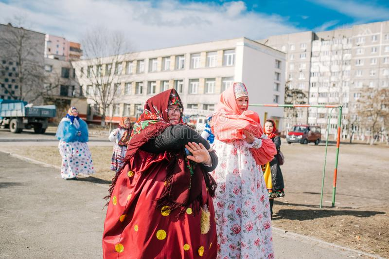 Two mature woman in folk costume dances in city park. The celebration of the Maslenitsa in the city stock photo