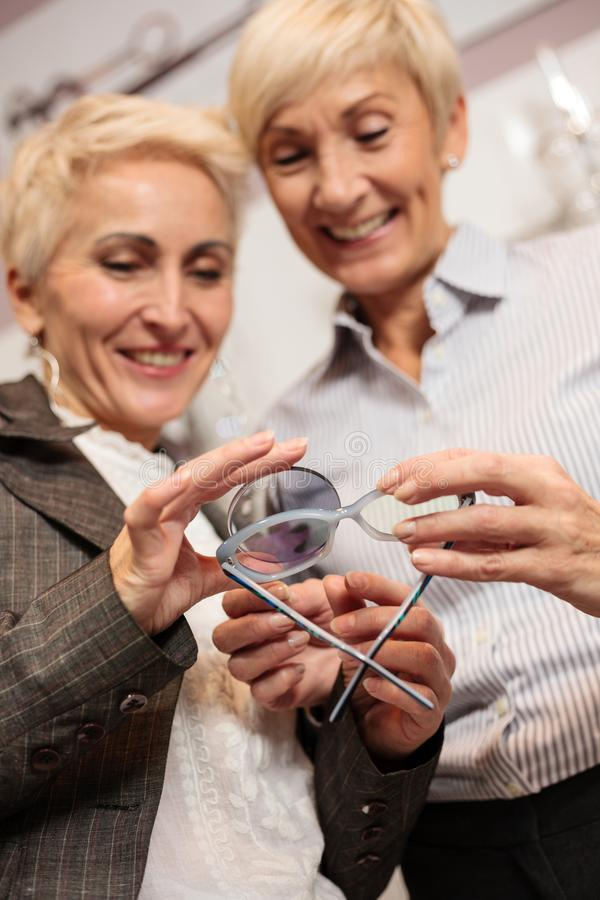 Two mature women choosing prescription lenses to match with new reading glasses royalty free stock photo