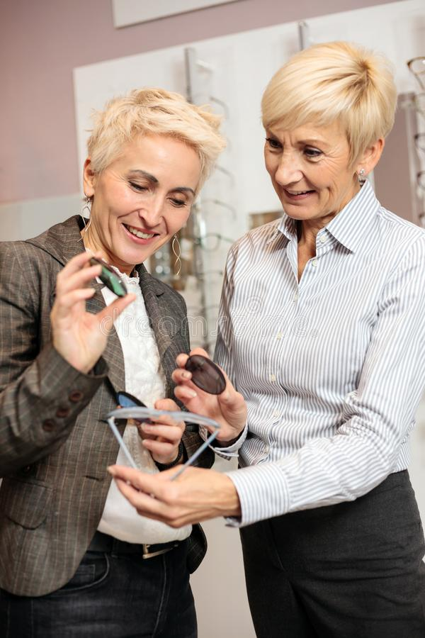 Two mature women choosing prescription lenses to match with new reading glasses royalty free stock photography