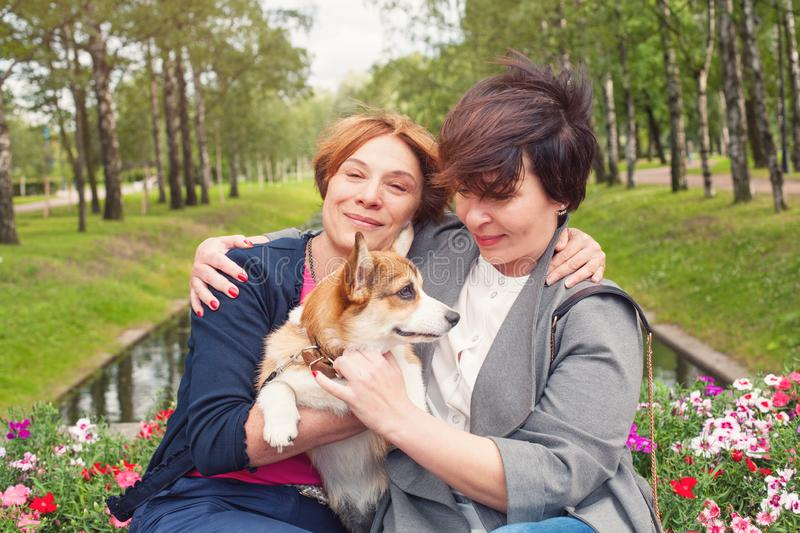 Two mature women with dog pet outdoor, lifestyle portrait royalty free stock image