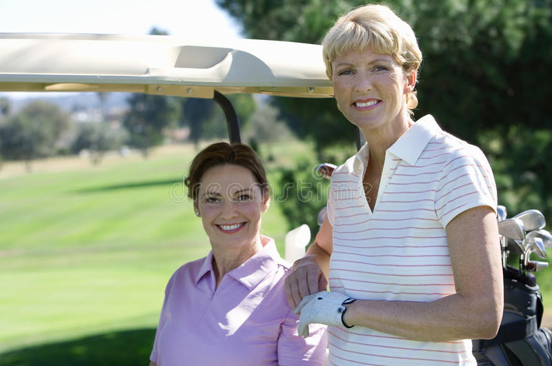 Two mature women posing on golf course, brunette sitting in golf buggy, blonde standing beside her, smiling, portrait stock photography