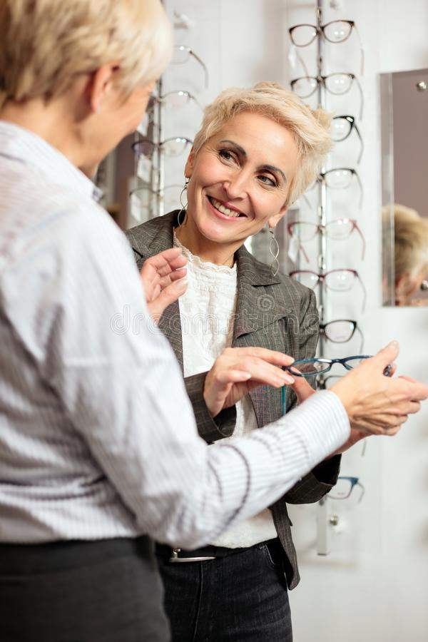 Two mature women shopping and choosing prescription eyeglasses royalty free stock images