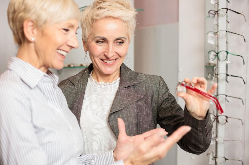 Two mature women shopping for prescription glasses, choosing and trying various models stock photography