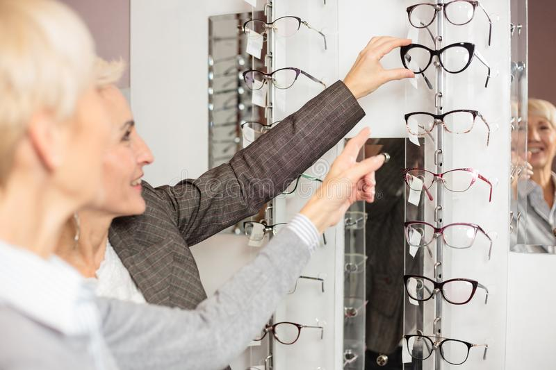 Two mature women shopping for prescription glasses, choosing and trying various models stock images