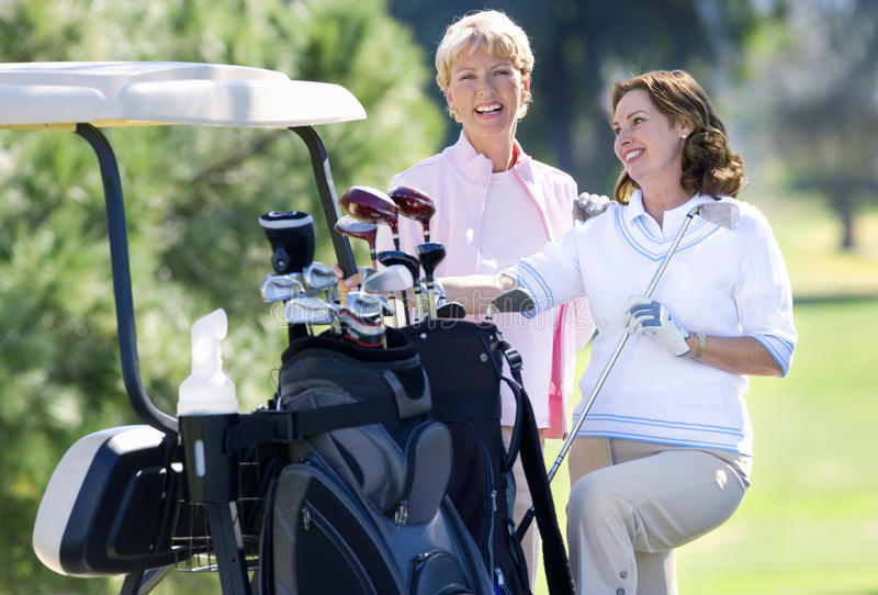 Two mature women standing beside parked golf buggy, playing golf, brunette holding golf club, smiling, portrait stock photo
