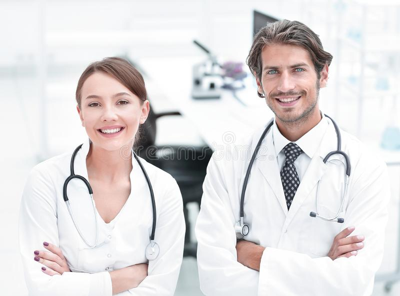 Portrait of two successful professional doctors workers in coats. Two medic colleagues in white coats stock images