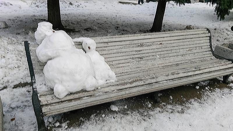 Two melted snowmen on a bench in the park royalty free stock photo