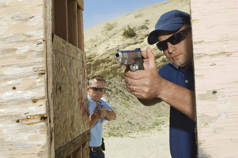 Two Men Aiming Hand Guns At Firing Range stock photography