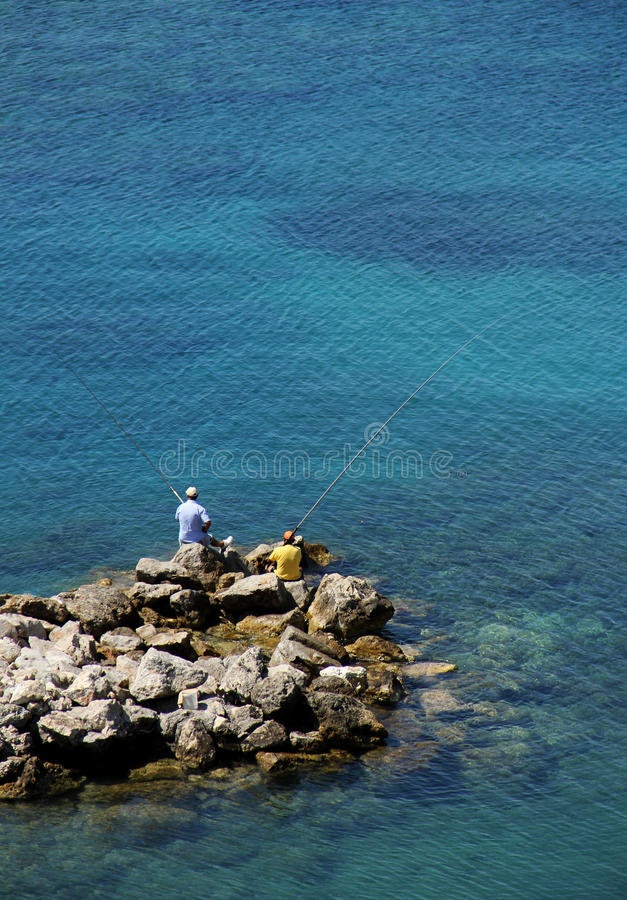 Two men angling seashore. Two men angling with rod and line on seashore stock photography