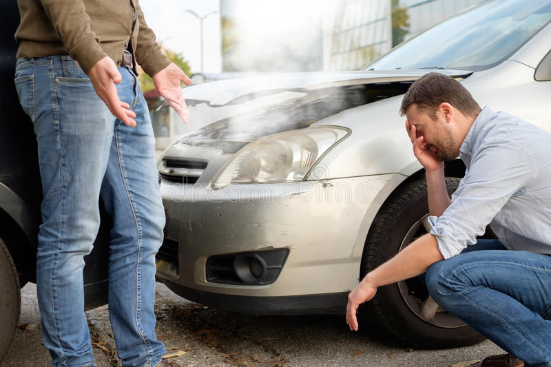 Two men arguing after a car accident. On the road royalty free stock images