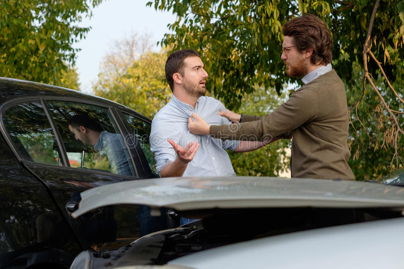 Two men arguing after a car accident on the road. Street stock image