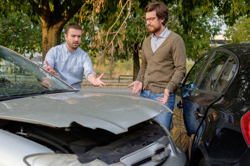 Two men arguing after a car accident on the road. Street royalty free stock image