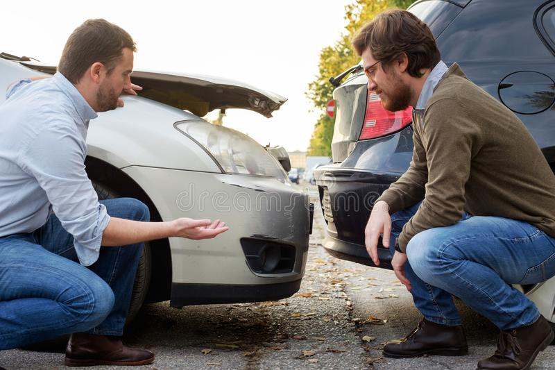 Two men arguing after a car accident on the road. Two men checking car damage after accident on the road royalty free stock photography