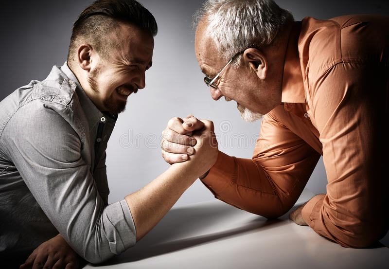 Two men arm wrestling competition. Two angry men arm wrestling competition on gray background royalty free stock photo
