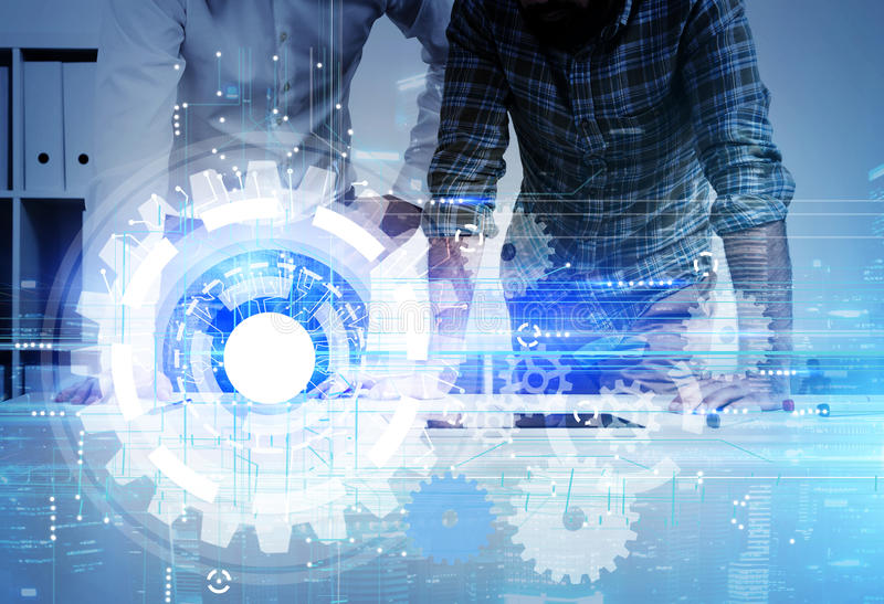 Two men and blue cogs. Two men in casual clothes standing in office. Large blue cogs on the foreground. Concept of engineering startup. Toned image. Double royalty free stock photos