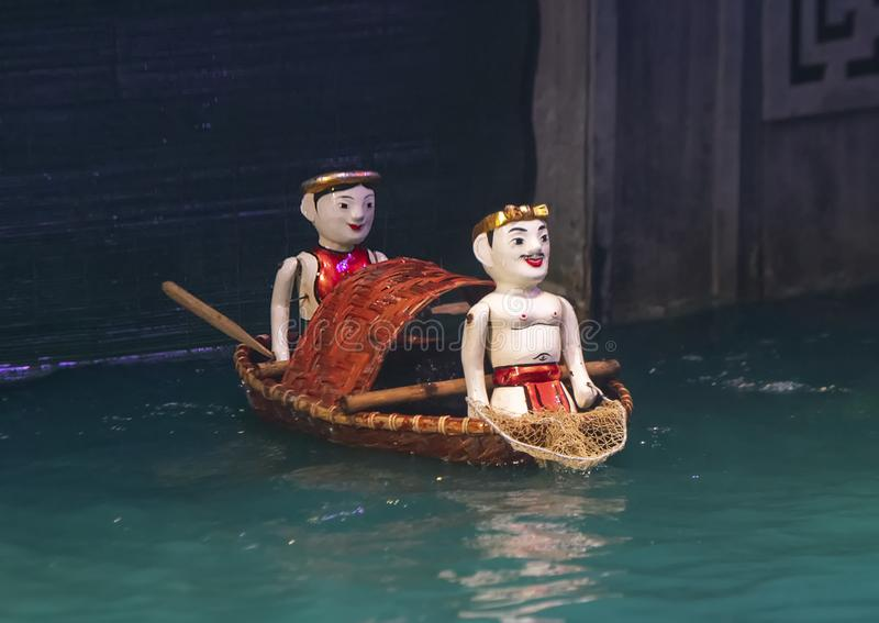 Two men in a boat water puppets in the Thang Long Water Puppet Theatre, Hanoi, Vietnam royalty free stock image