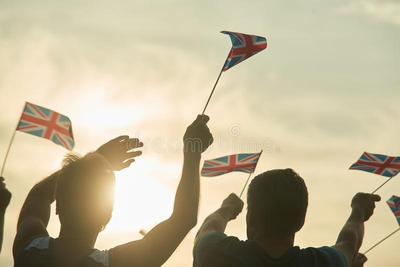 Two men with british flags. Cloudy and sunny sky background royalty free stock images