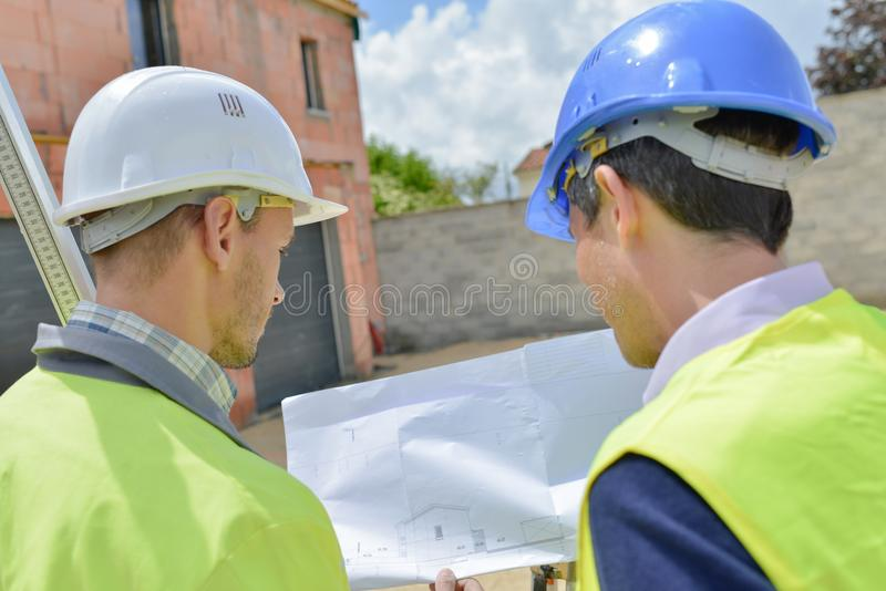 Two men on building site looking at plans stock image
