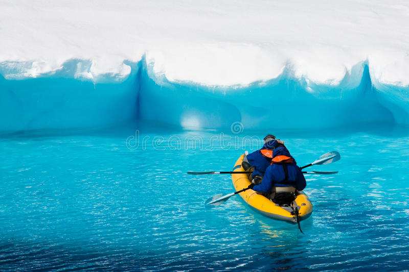 Two men in a canoe. Among icebergs in Antarctica stock image