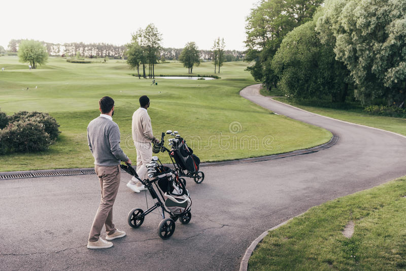 Two men carrying golf clubs in golf bags and walking at golf course royalty free stock image