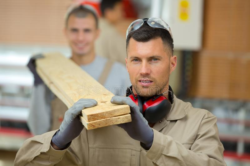 Two men carrying wood on their shoulders stock images